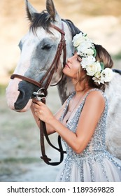 Bride. Beautiful woman in flower wreath and beautiful dress with horse outdoor.