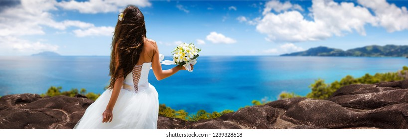 bride, beautiful young girl with dark hair in a white wedding dress with bouquet on  background of beach with blue water. Seychelles