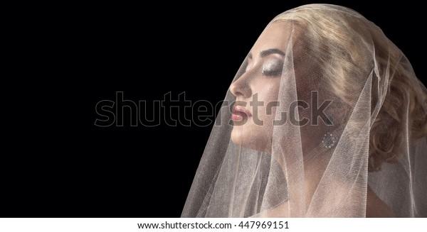 Bride behind her veil - detail of her face. Romantic photo on back background. Wedding bouquet, an elegant woman with closed eyes. Stunning beautiful bride with curly hair looks hidden under a veil
