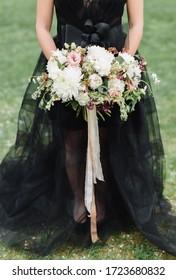 Bride in black wedding dress with wedding bouquet in her hands. Bride holds a wedding bouquet