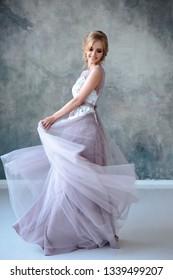 Brautblonde Frau in einem modernen Hochzeitskleid mit elegantem Friseur und Make-up. Fashion Beauty-Portrait auf strukturiertem Hintergrund