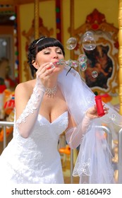 The bride blows soap bubbles