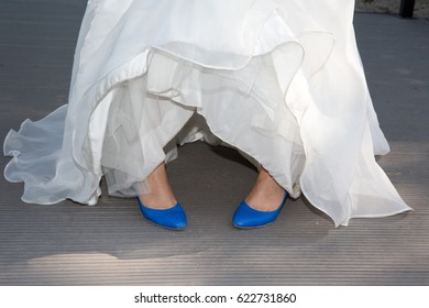 Bride in blue shoes in white dress