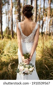 bride with a bouquet from the back in the forest
