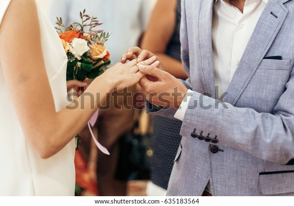bride with bouquet and groom exchanging wedding rings at wedding registry. stylish couple official wedding ceremony