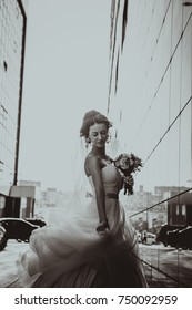 Bride and bouquet on backround mirror buildings