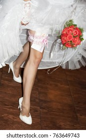 The bride with a bouquet shows the garter