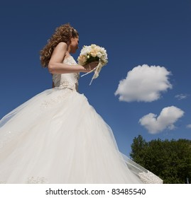 The bride with a bouquet and the sky. The bride in a wedding dress with a bouquet with clouds.