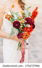 The bride bragging in the arms of a wedding bouquet. Red flowers and eucalyptus. The bouquet is vintage with bright colors.