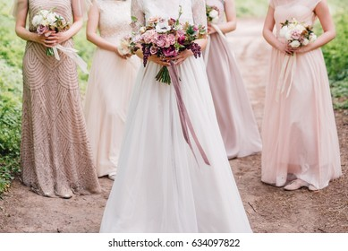 Bride and bridesmaid are holding bouquets of flowers in hands. Bridesmaid are on background. Wedding. Details.