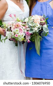 bride and bridesmaid  holding their wedding bouquet of flowers with grey and green ribbons and pink and purple flowers