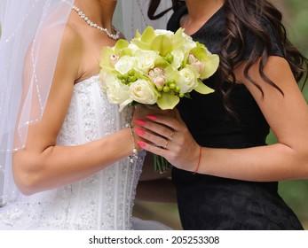 bride and bridesmaid holding wedding bouquet