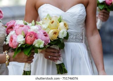 Bride bridesmaid holding wedding flower bouquet