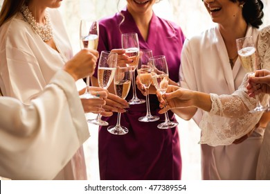 Bride and bridesmaids celebrate and drink champagne from glasses