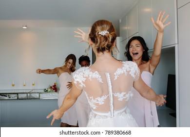 Bride and bridesmaids having fun in hotel room on wedding day. Bridesmaids hugging bride on wedding day.