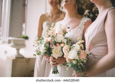 A bride and bridesmaids holding their bouquets and laughing.