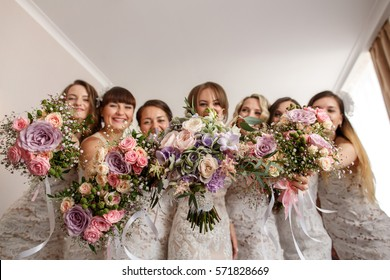 Bride and bridesmaids holding wedding bouquets and having fun at wedding day