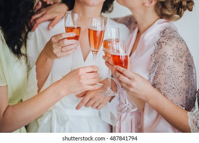 Bride and bridesmaids are hugging and are holding champagne glasses