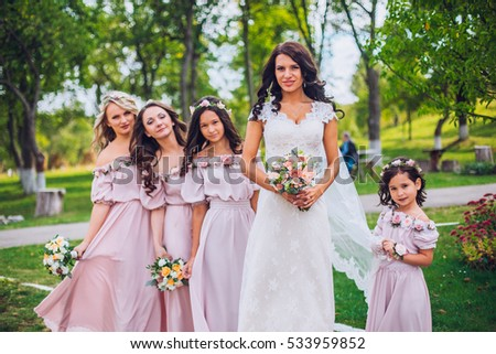 c2533364d2 Bride with bridesmaids and little girl kids in the same color dress posing  on camera in