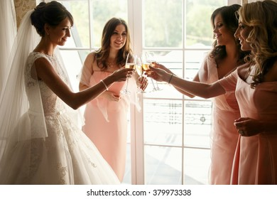 Bride and bridesmaids on the wedding day in hotel room