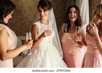 Bride and bridesmaids on the wedding day drinking wine