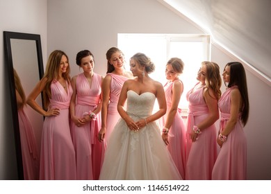 Bride and bridesmaids in pink dresses posing at wedding day. Happy marriage and wedding party concept