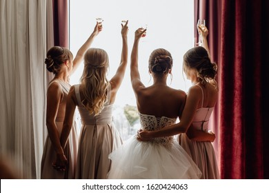 Bride with Bridesmaids Raised Glasses Rear View. Hugging Attractive Stylish Women Standing Together near Window with Alcoholic Beverage Champagne in Wineglasses. Horizontal Photography