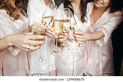 Bride and bridesmaids stand in silk robes with glasses of champagne
