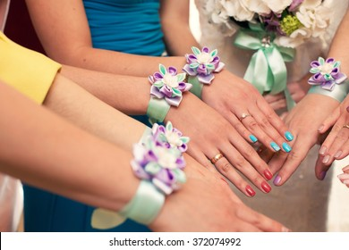 bride and bridesmaids with violet bracelets on hands