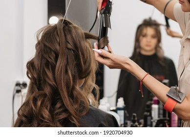 bride with brown curly long hair in a beauty salon is preparing for the wedding day in the morning