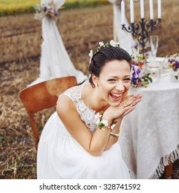 Bride burst of laughing, sitting near wedding decorations on table.