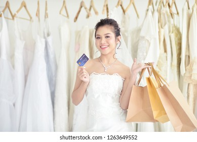 Bride carrying shopping bags and showing credit card.