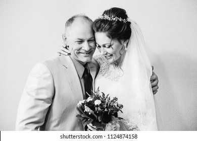 The bride in a chic dress and a wedding veil holds the bouquet with her father on a black and white photograph