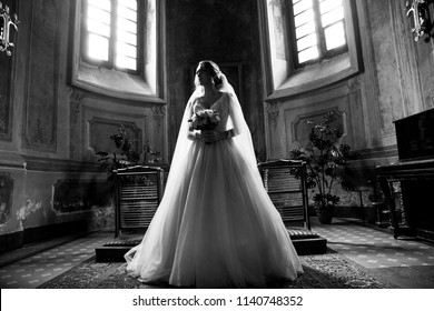 The bride in the Church.Beautiful wedding photos.Wedding dress and Bridal bouquet.Black white photo
