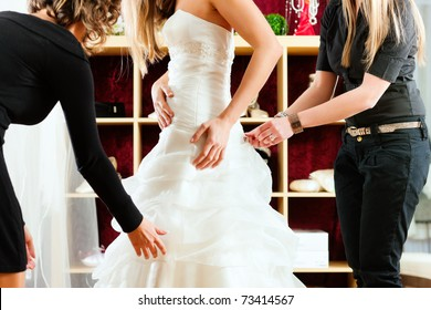 Bride at the clothes shop for wedding dresses; she is choosing a dress and the designer are assisting her