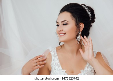 The bride corrects the earring, Beautiful earrings and hands of the bride. Wedding day.  Happy woman bride in home prepared to wedding ceremony.