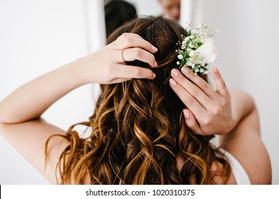 The bride corrects wreath of flowers at his head. A look on the back of the woman's hands and hair. Wedding Morning.