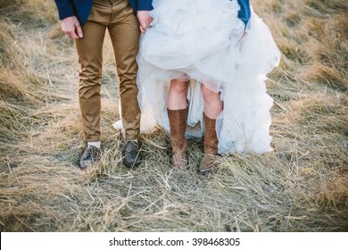 Bride in cowboy boots and groom in brown shoes stand side by side at sunset field. Shallow focus.