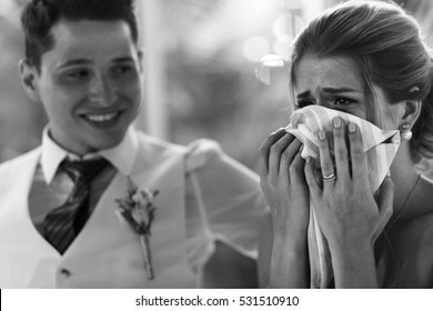 Bride cries in napkin while groom hugs her