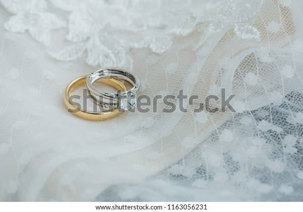 Bride diamond rings   and groom gold wedding band on delicate lace wedding dress detail close up just before wedding