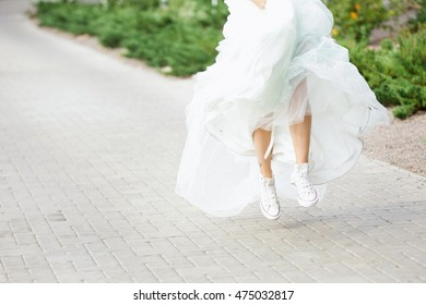 Bride dressed in long wedding dress and sneakers, running and jumping in a park.