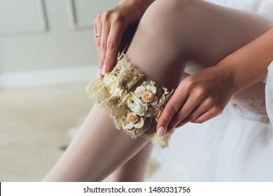 bride dresses garter on the leg. Picture of beautiful female barefoot legs in wedding dress. Bride dresses stockings on feet. Bride putting a wedding garter on her leg.