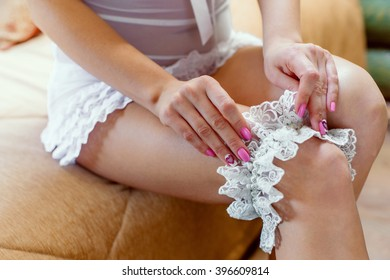 Bride dresses garter on the leg.Picture of beautiful female barefoot legs in wedding dress.