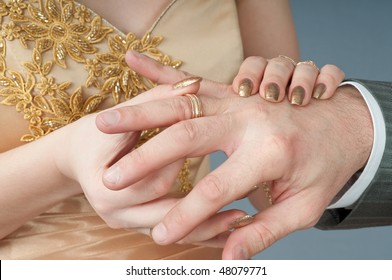 The bride dresses to the groom on a finger a gold ring.