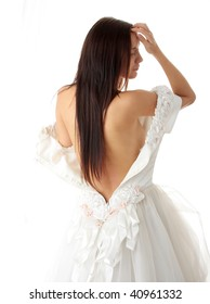 Bride dressing up her wedding dress on nude body, isolated