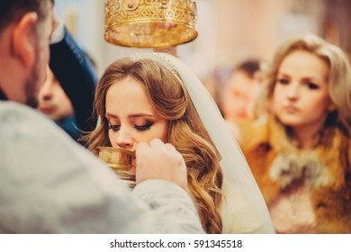 Bride drinks holdy water during the ceremony in church