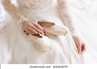 Bride in elegant classic wedding dress with shoes . Morning of the bride. Ballerina with pointe shoes