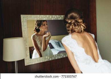 Bride in elegant dress looking in the mirror