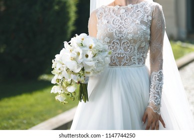 bride in elegant lace dress with orchid bouquet