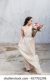 Bride in an elegant silk dress with a bouquet of flowers